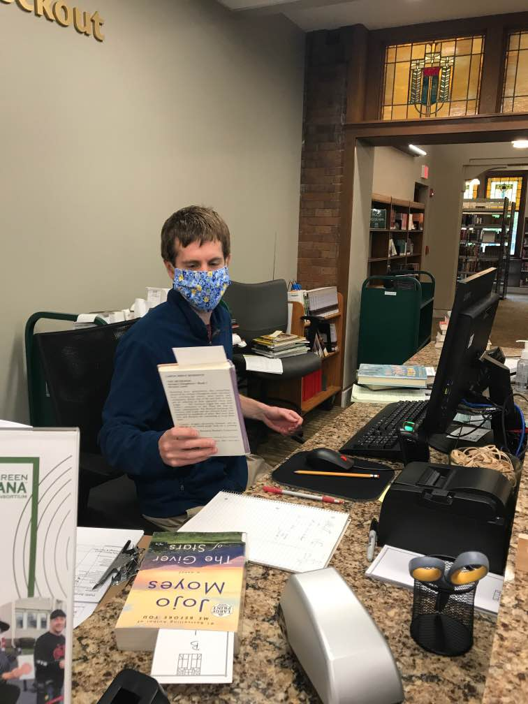 Programming Specialist Zach Heimach scans books while wearing a mask at the main library.